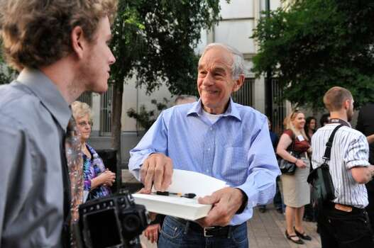 GOP presidential candidate Ron Paul signs a copy of his book after speaking to supporters at a rally in Main Plaza on Thursday, April 12, 2012.