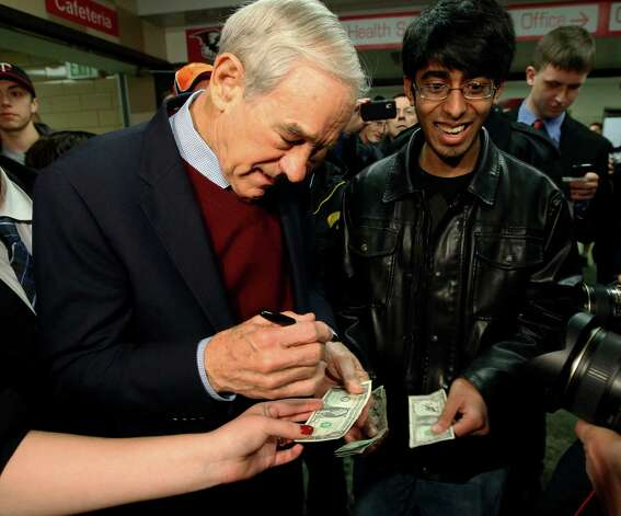 Republican presidential candidate Rep. Ron Paul, R-Texas, signs an autograph on a dollar bill as he visits a caucus site Tuesday, Feb. 7, 2012, in Coon Rapids, Minn. (AP Photo/Charles Rex Arbogast) Photo: Charles Rex Arbogast, Associated Press / AP