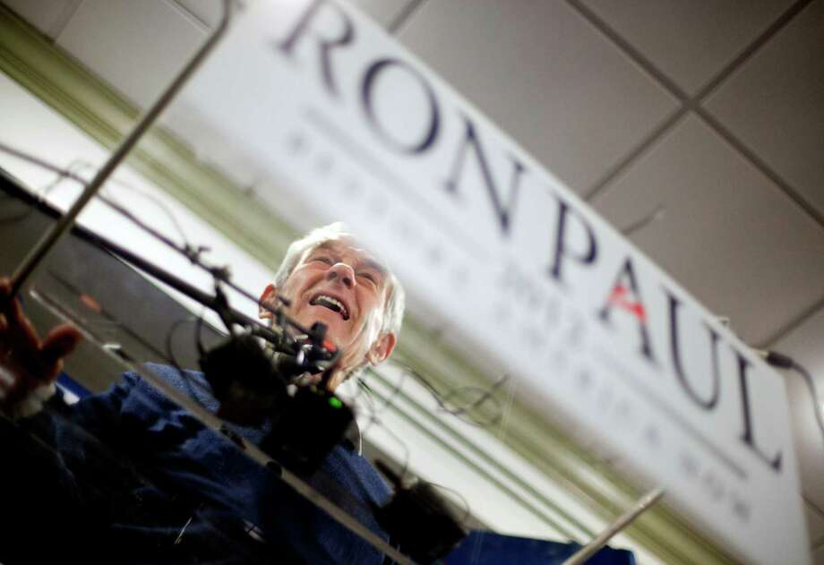 Republican presidential candidate Rep. Ron Paul, R-Texas, is seen through a plexiglass podium as he speaks during a campaign stop Tuesday, Jan. 17, 2012, in Rock Hill, S.C. (AP Photo/David Goldman) Photo: David Goldman, Associated Press / AP