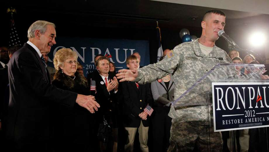 In this Jan. 3, 2012 photo, Republican presidential candidate Rep. Ron Paul, R-Texas, left, listens as Cpl. Jesse Thorsen, right, speaks during his caucus night rally, in Ankeny, Iowa. Thorsen, an Army reservist who expressed his support for Paul when he took the stage with the Republican presidential candidate, could face legal troubles, the military said on Thursday, Jan. 5. Army Reserve spokeswoman Maj. Angel Wallace said participating in a partisan political event in uniform is a violation of Defense Department rules, and the military is reviewing whether Thorsen could face legal ramifications. (AP Photo/Eric Gay) Photo: Eric Gay, Associated Press / AP