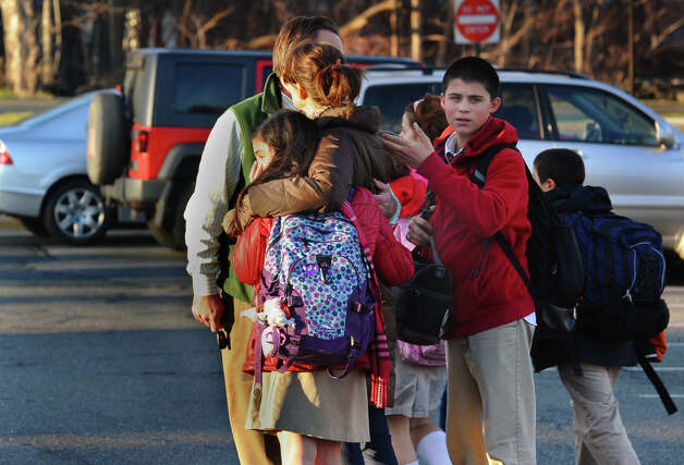 After a horrific shooting at Sandy Hook Elementary School nearby, parents and children leave St. Rose School after a lockdown at the school in Newtown, Conn. on Friday December 14, 2012. Photo: Christian Abraham / Connecticut Post