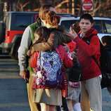 After a horrific shooting at Sandy Hook Elementary School nearby, parents and children leave St. Rose School after a lockdown at the school in Newtown, Conn. on Friday December 14, 2012.