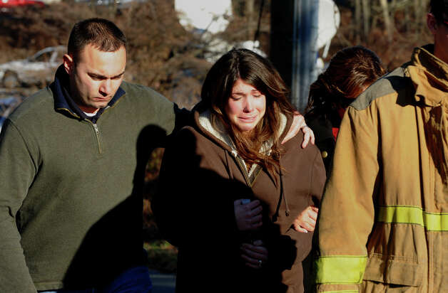 A grief stricken couple leave the Sandy Hook Firestation in Newtown, Conn., following the shootings at nearby Sandy Hook Elementary School on Friday, Dec. 14, 2012. Photo: Christian Abraham / Connecticut Post