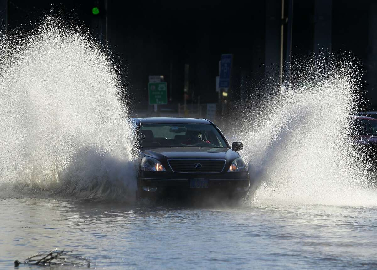 A commuter drives through a flooded portion of Shoreline Highway below Highway 101 during a king tide in Mill Valley, Calif. on Thursday, Dec. 13, 2012.