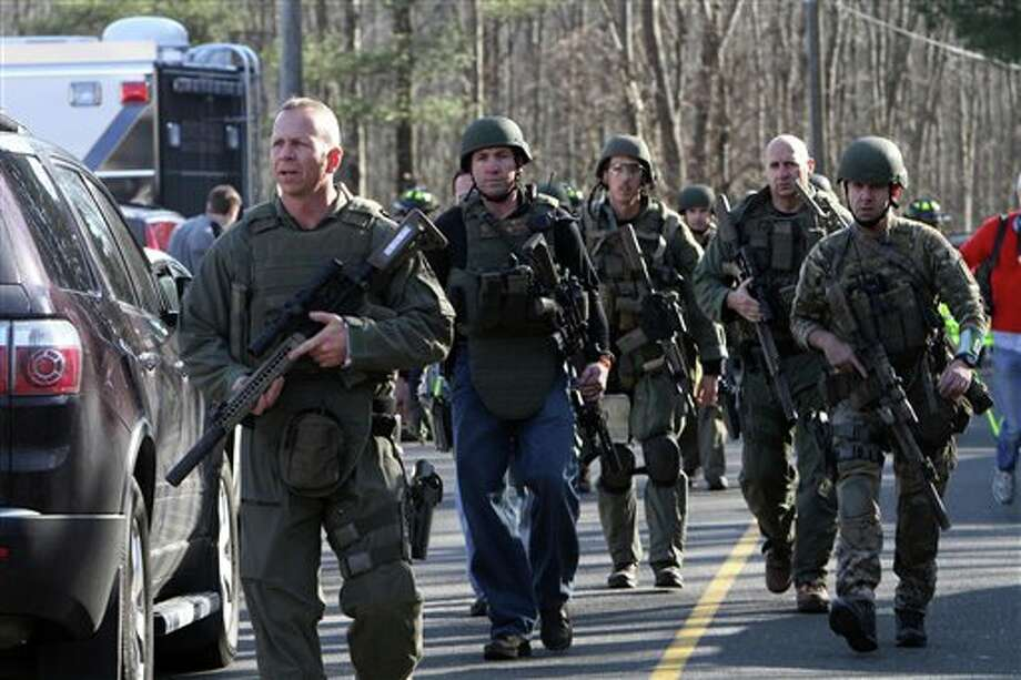 Heavily armed Connecticut State troopers are on the scene at the Sandy Hook School following a shooting at the school, Friday, Dec. 14, 2012 in Newtown, Conn. A man opened fire inside the Connecticut elementary school where his mother worked Friday, killing 26 people, including 18 children, and forcing students to cower in classrooms and then flee with the help of teachers and police. (AP Photo/The Journal News, Frank Becerra Jr.) MANDATORY CREDIT, NYC OUT, NO SALES, TV OUT, NEWSDAY OUT; MAGS OUT Photo: Frank Becerra Jr., AP / The Journal News