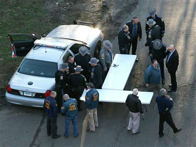 Officials stand by a triage area near Sandy Hook Elementary School in Newtown, Conn., where authorities say a gunman opened fire inside the school in a shooting that left 27 people dead, including 20 children, Friday, Dec. 14, 2012. (AP Photo/Julio Cortez) Photo: Julio Cortez, AP / AP