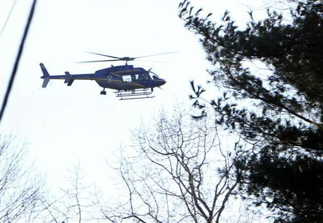 A Connecticut State Police helicopter hovers over the scene near the Sandy Hook School following a shooting , Friday, Dec. 14, 2012 in Newtown, Conn.(AP Photo/The Journal News, Frank Becerra Jr.) MANDATORY CREDIT, NYC OUT, NO SALES, TV OUT, NEWSDAY OUT; MAGS OUT Photo: Frank Becerra Jr., AP / The Journal News