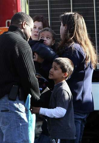 Schoolchildren wait for their parents at the Sandy Hook firehouse following a mass shooting at Sandy Hook Elementary School, Friday, Dec. 14, 2012 in Newtown, Conn.  (AP Photo/The Journal News, Frank Becerra Jr.) MANDATORY CREDIT, NYC OUT, NO SALES, TV OUT, NEWSDAY OUT; MAGS OUT Photo: Frank Becerra Jr., AP / The Journal News
