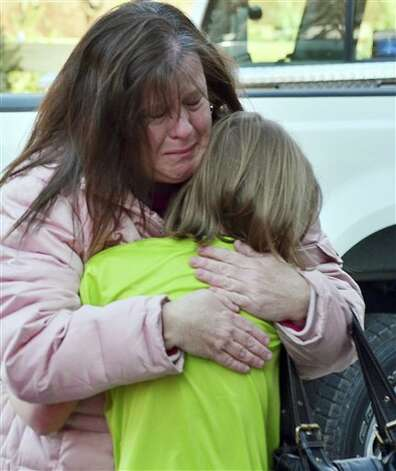 A mother hugs her daughter following a shooting at the Sandy Hook Elementary School in Newtown, Conn., about 60 miles (96 kilometers) northeast of New York City, Friday, Dec. 14, 2012. A gunman entered the school Friday morning and killed at least 26 people, including 20 young children. (AP Photo/The New Haven Register, Melanie Stengel) Photo: Melanie Stengel, AP / The New Haven Register