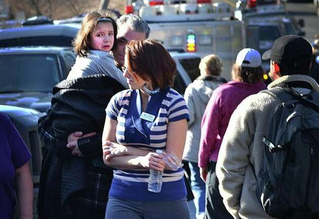 A young girl is comforted following a shooting at the Sandy Hook Elementary School in Newtown, Conn., about 60 miles (96 kilometers) northeast of New York City, Friday, Dec. 14, 2012. A gunman entered the school Friday morning and killed at least 26 people, including 20 young children. (AP Photo/The New Haven Register, Melanie Stengel) Photo: Melanie Stengel, AP / The New Haven Register