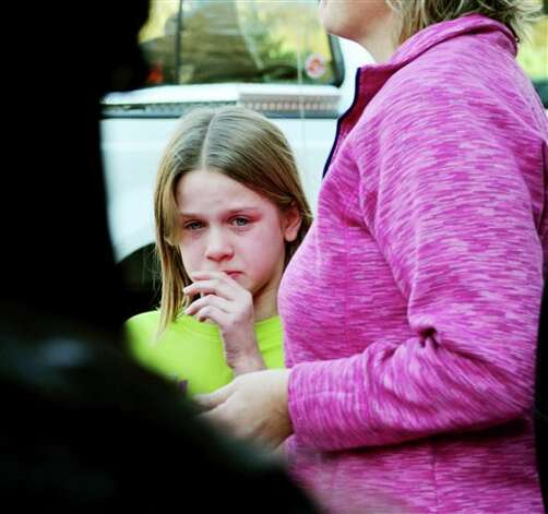 A young girl cires following a shooting at the Sandy Hook Elementary School in Newtown, Conn., about 60 miles (96 kilometers) northeast of New York City, Friday, Dec. 14, 2012. A gunman entered the school Friday morning and killed at least 26 people, including 20 young children. (AP Photo/The New Haven Register, Melanie Stengel) Photo: Melanie Stengel, AP / The New Haven Register