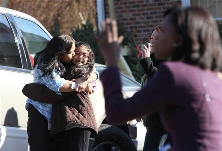 A woman hugs her daughter after being reunited at the Sandy Hook firehouse following a mass shooting at the Sandy Hook Elementary School, Friday, Dec. 14, 2012 in Newtown, Conn.  (AP Photo/The Journal News, Frank Becerra Jr.) MANDATORY CREDIT, NYC OUT, NO SALES, TV OUT, NEWSDAY OUT; MAGS OUT Photo: Frank Becerra Jr., AP / The Journal News