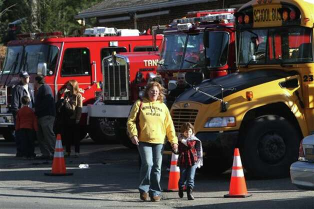 Parents walk away from the Sandy Hook  Elementary School with their children following a shooting at the school, Friday, Dec. 14, 2012 in Newtown, Conn.  (AP Photo/The Journal News, Frank Becerra Jr.) MANDATORY CREDIT, NYC OUT, NO SALES, TV OUT, NEWSDAY OUT; MAGS OUT Photo: Frank Becerra Jr., AP / The Journal News