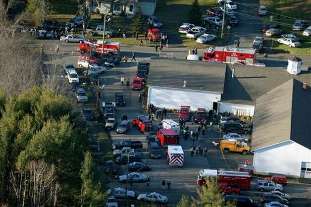 This aerial photo shows a triage area set up at the Sandy Hook fire station in Newtown, Conn., near where authorities say a gunman opened fire inside Sandy Hook Elementary School in a shooting that left 27 people dead, including 18 children, Friday, Dec. 14, 2012. (AP Photo/Julio Cortez) Photo: Julio Cortez, AP / AP