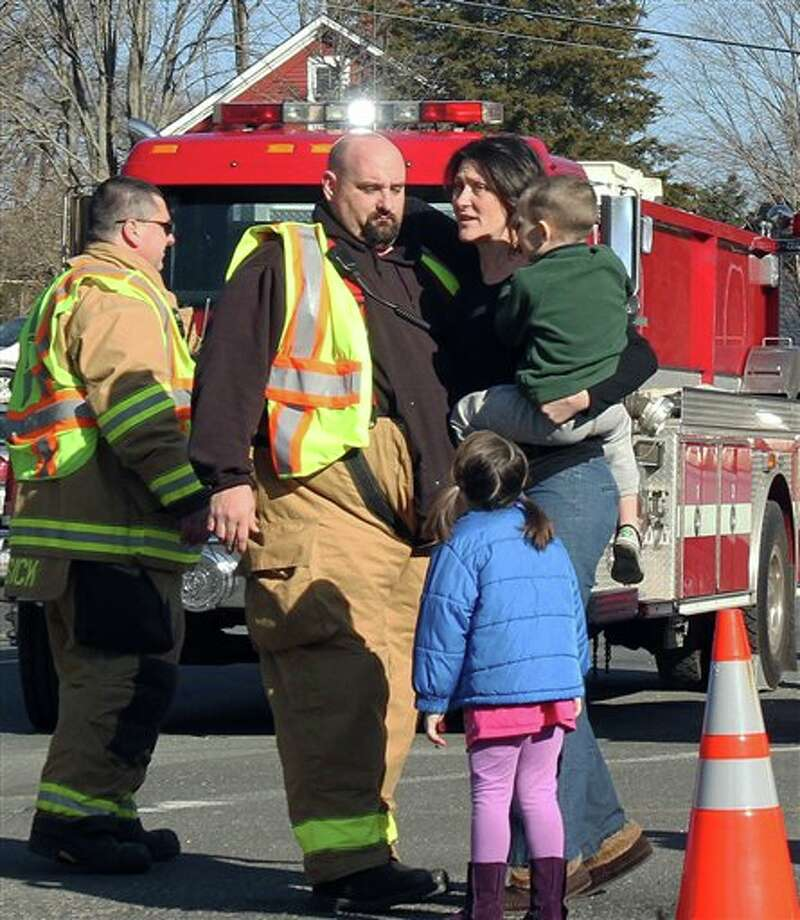 A woman holding her children embraces a firefighter after a shooting at the Sandy Hook Elementary School in Newtown, Conn. on Friday, Dec. 14, 2012. (AP Photo/The Journal News, Frank Becerra Jr.) NYC OUT, NO SALES, TV OUT, NEWSDAY OUT; MAGS OUT; MANDATORY CREDIT: THE JOURNAL NEWS, FRANK BECERRA JR. Photo: Frank Becerra Jr., AP / The Journal News