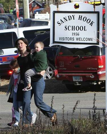 A parent walks away from the Sandy Hook Elementary School with her children following a shooting at the school in Newtown, Conn. on Friday, Dec. 14, 2012. (AP Photo/The Journal News, Frank Becerra Jr.) NYC OUT, NO SALES, TV OUT, NEWSDAY OUT; MAGS OUT; MANDATORY CREDIT: THE JOURNAL NEWS, FRANK BECERRA JR. Photo: Frank Becerra Jr., ASSOCIATED PRESS / The Journal News2012