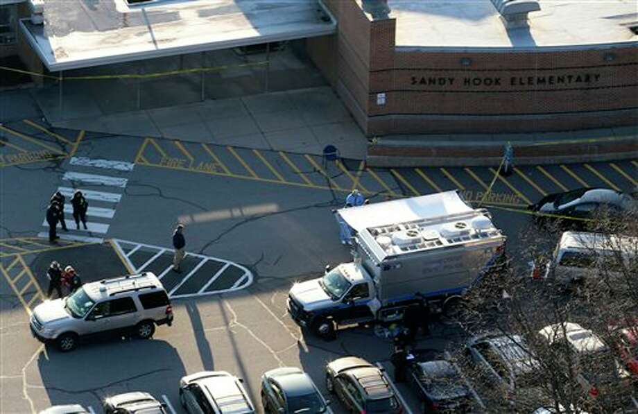 Officials are on the scene outside of Sandy Hook Elementary School in Newtown, Conn., where authorities say a gunman opened fire inside an elementary school in a shooting that left 27 people dead, including 18 children, Friday, Dec. 14, 2012. (AP Photo/Julio Cortez) Photo: Julio Cortez, ASSOCIATED PRESS / AP2012