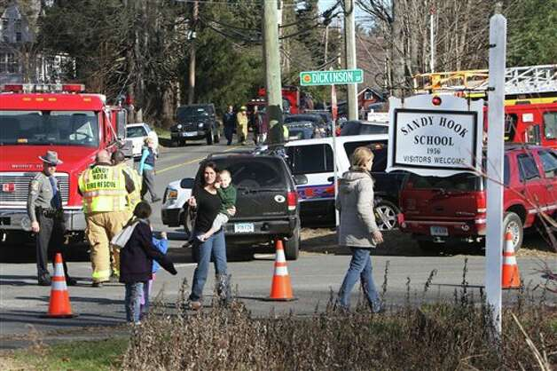 Parents walk away from the Sandy Hook  Elementary School with their children following a shooting, Friday, Dec. 14, 2012 in Newtown, Conn. A man opened fire inside the Connecticut elementary school where his mother worked Friday, killing 26 people, including 18 children, and forcing students to cower in classrooms and then flee with the help of teachers and police. (AP Photo/The Journal News, Frank Becerra Jr.) MANDATORY CREDIT, NYC OUT, NO SALES, TV OUT, NEWSDAY OUT; MAGS OUT Photo: Frank Becerra Jr., AP / The Journal News