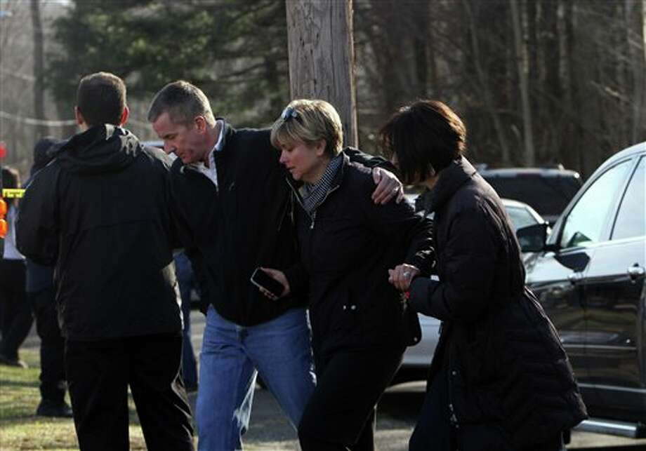 Teachers walk away from the Sandy Hook School following a shooting  at the school, Friday, Dec. 14, 2012 in Newtown, Conn. A man opened fire inside the Connecticut elementary school where his mother worked Friday, killing 26 people, including 18 children, and forcing students to cower in classrooms and then flee with the help of teachers and police. (AP Photo/The Journal News, Frank Becerra Jr.) MANDATORY CREDIT, NYC OUT, NO SALES, TV OUT, NEWSDAY OUT; MAGS OUT Photo: Frank Becerra Jr., AP / The Journal News