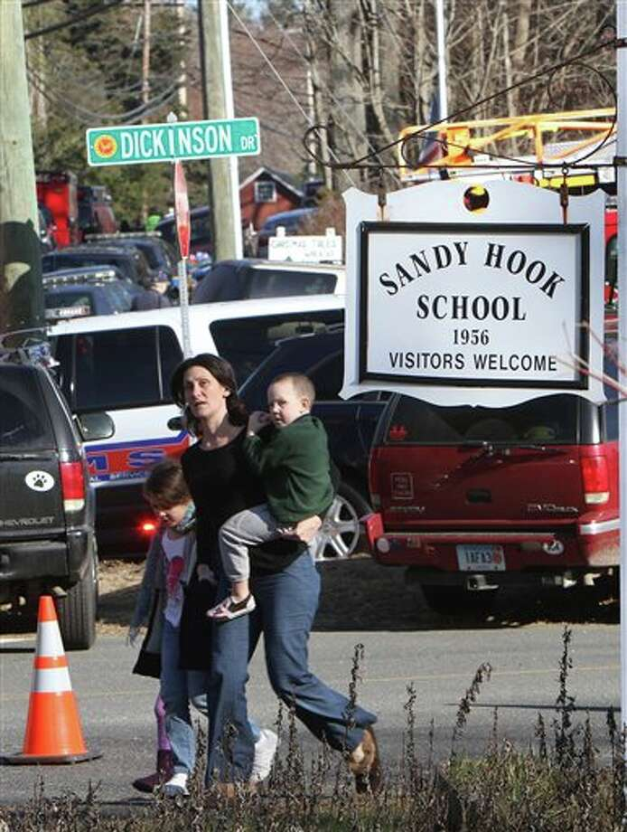 Parents walk away from the Sandy Hook Elementary School with their children following a shooting at the school in Newtown, Conn. on Friday, Dec. 14, 2012. (AP Photo/The Journal News, Frank Becerra Jr.) NYC OUT, NO SALES, TV OUT, NEWSDAY OUT; MAGS OUT; MANDATORY CREDIT: THE JOURNAL NEWS, FRANK BECERRA JR. Photo: Frank Becerra Jr., AP / The Journal News
