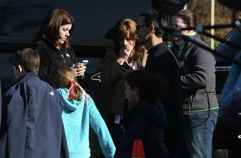A woman weeps as she arrives to pick up her children at the Sandy Hook Elementary School, Friday, Dec. 14, 2012 in Newtown, Conn. A man opened fire inside the Connecticut elementary school where his mother worked Friday, killing 26 people, including 18 children, and forcing students to cower in classrooms and then flee with the help of teachers and police. (AP Photo/The Journal News, Frank Becerra Jr.) MANDATORY CREDIT, NYC OUT, NO SALES, TV OUT, NEWSDAY OUT; MAGS OUT Photo: Frank Becerra Jr., AP / The Journal News