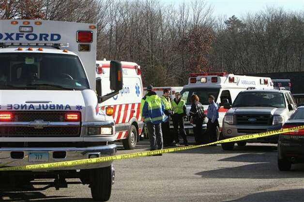 Emergency personnel work the scene outside Sandy Hook Elementary School after a mass shooting Friday, Dec. 14, 2012 in Newtown, Conn. A man opened fire inside the Connecticut elementary school where his mother worked Friday, killing 26 people, including 18 children, and forcing students to cower in classrooms and then flee with the help of teachers and police. (AP Photo/The Journal News, Frank Becerra Jr.) MANDATORY CREDIT, NYC OUT, NO SALES, TV OUT, NEWSDAY OUT; MAGS OUT Photo: Frank Becerra Jr., AP / The Journal News