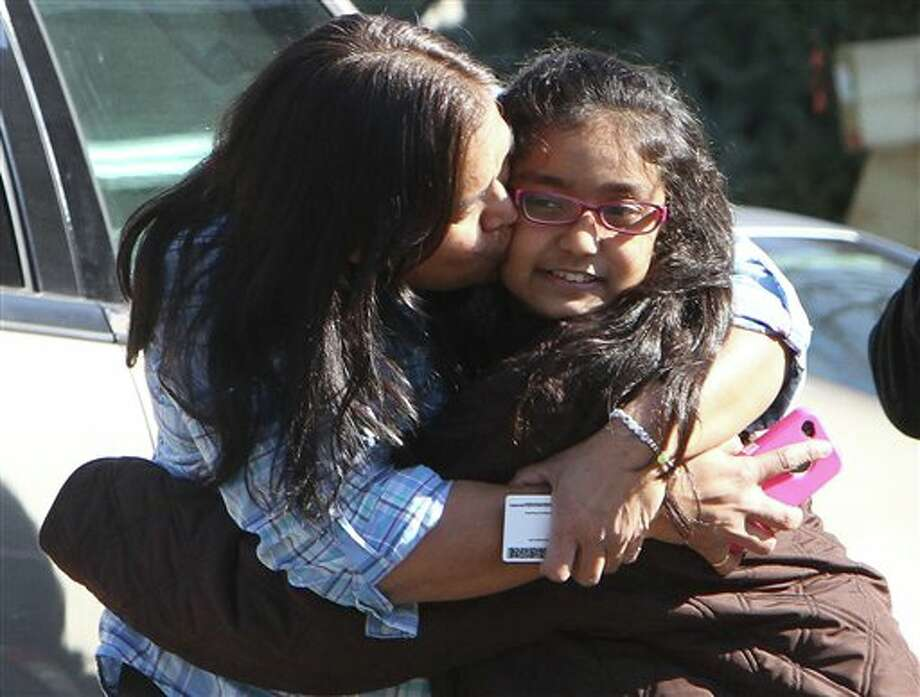 A woman hugs her daughter after being reunited at the Sandy Hook firehouse after a mass shooting at the Sandy Hook Elementary School in Newtown, Conn. on Friday, Dec. 14, 2012. (AP Photo/The Journal News, Frank Becerra Jr.) NYC OUT, NO SALES, TV OUT, NEWSDAY OUT; MAGS OUT; MANDATORY CREDIT: THE JOURNAL NEWS, FRANK BECERRA JR. Photo: Frank Becerra Jr., AP / The Journal News