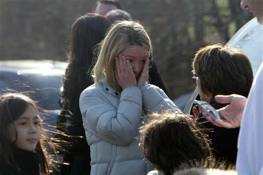 A woman weeps as she arrives to pick up her children at the Sandy Hook Elementary School, Friday, Dec. 14, 2012 in Newtown, Conn. A man opened fire inside the Connecticut elementary school where his mother worked Friday, killing 26 people, including 18 children, and forcing students to cower in classrooms and then flee with the help of teachers and police. (AP Photo/The Journal News, Frank Becerra Jr.) MANDATORY CREDIT, NYC OUT, NO SALES, TV OUT, NEWSDAY OUT; MAGS OUT Photo: Frank Becerra Jr., ASSOCIATED PRESS / The Journal News2012