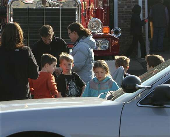 School children wait for their parents at the Sandy Hook firehouse following a mass shooting at the Sandy Hook Elementary School  Friday, Dec. 14, 2012 in Newtown, Conn. A man opened fire inside the Connecticut elementary school where his mother worked Friday, killing 26 people, including 18 children, and forcing students to cower in classrooms and then flee with the help of teachers and police. (AP Photo/The Journal News, Frank Becerra Jr.) MANDATORY CREDIT, NYC OUT, NO SALES, TV OUT, NEWSDAY OUT; MAGS OUT Photo: Frank Becerra Jr., ASSOCIATED PRESS / The Journal News2012