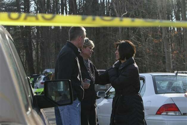 Teachers walk away from the Sandy Hook School following a shooting at the school Friday, Dec. 14, 2012 in Newtown, Conn. A man opened fire inside the Connecticut elementary school where his mother worked Friday, killing 26 people, including 18 children, and forcing students to cower in classrooms and then flee with the help of teachers and police. (AP Photo/The Journal News, Frank Becerra Jr.) MANDATORY CREDIT, NYC OUT, NO SALES, TV OUT, NEWSDAY OUT; MAGS OUT Photo: Frank Becerra Jr., AP / The Journal News