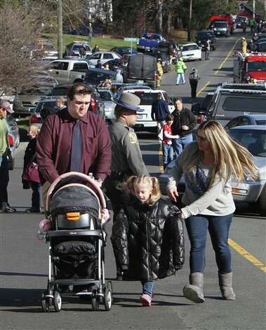 Parents walk away from the Sandy Hook School with their children following a shooting at the school Friday, Dec. 14, 2012 in Newtown, Conn. A man opened fire inside the Connecticut elementary school where his mother worked Friday, killing 26 people, including 18 children, and forcing students to cower in classrooms and then flee with the help of teachers and police. (AP Photo/The Journal News, Frank Becerra Jr.) MANDATORY CREDIT, NYC OUT, NO SALES, ONLINE OUT, TV OUT, NEWSDAY OUT; MAGS OUT Photo: Frank Becerra Jr., ASSOCIATED PRESS / The Journal News2012