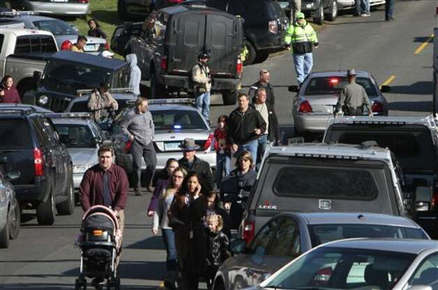 Parents walk away from the Sandy Hook School with their children following a shooting at the school Friday, Dec. 14, 2012 in Newtown, Conn. A man opened fire inside the Connecticut elementary school where his mother worked Friday, killing 26 people, including 18 children, and forcing students to cower in classrooms and then flee with the help of teachers and police. (AP Photo/The Journal News, Frank Becerra Jr.) MANDATORY CREDIT, NYC OUT, NO SALES, ONLINE OUT, TV OUT, NEWSDAY OUT; MAGS OUT Photo: Frank Becerra Jr., AP / The Journal News