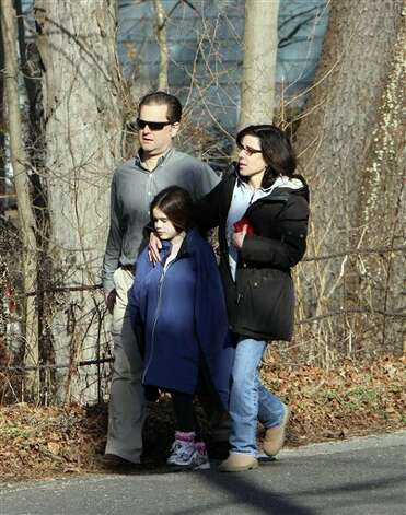 Parents walk away from the Sandy Hook School with their children following a shooting at the school Friday, Dec. 14, 2012.  A man opened fire inside the Connecticut elementary school where his mother worked Friday, killing 26 people, including 18 children, and forcing students to cower in classrooms and then flee with the help of teachers and police. (AP Photo/The Journal News, Frank Becerra Jr.) MANDATORY CREDIT, NYC OUT, NO SALES, ONLINE OUT, TV OUT, NEWSDAY INTERNET OUT; MAGS OUT Photo: Frank Becerra Jr., AP / The Journal News