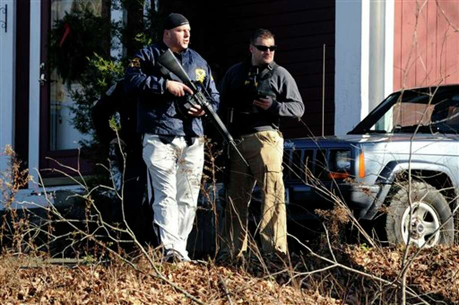 Law enforcement canvass an area following a shooting at the Sandy Hook Elementary School in Newtown, Conn., about 60 miles (96 kilometers) northeast of New York City, Friday, Dec. 14, 2012. An official with knowledge of Friday's shooting said 27 people were dead, including 18 children.  (AP Photo/Jessica Hill) Photo: Jessica Hill, ASSOCIATED PRESS / A2012