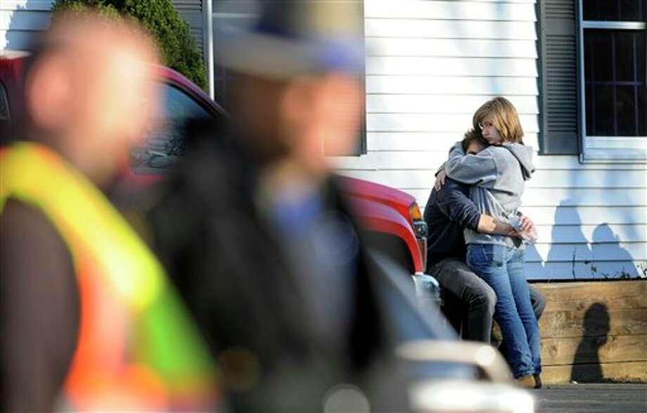 People embrace at a firehouse staging area for family around near the scene of a shooting at the Sandy Hook Elementary School in Newtown, Conn., about 60 miles (96 kilometers) northeast of New York City, Friday, Dec. 14, 2012. An official with knowledge of Friday's shooting said 27 people were dead, including 18 children.  (AP Photo/Jessica Hill) Photo: Jessica Hill, ASSOCIATED PRESS / A2012