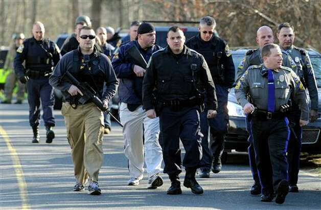 Law enforcement canvass the area following a shooting at the Sandy Hook Elementary School in Newtown, Conn., about 60 miles (96 kilometers) northeast of New York City, Friday, Dec. 14, 2012. An official with knowledge of Friday's shooting said 27 people were dead, including 18 children.  (AP Photo/Jessica Hill) Photo: Jessica Hill, ASSOCIATED PRESS / A2012