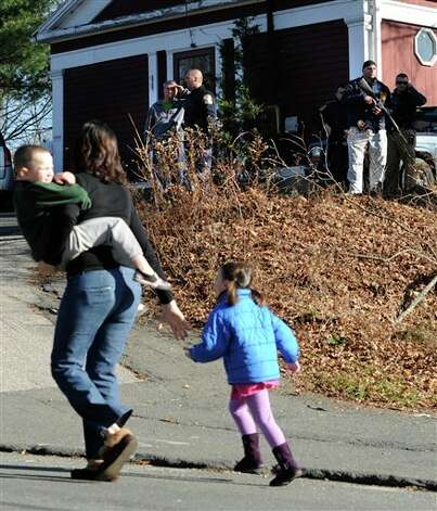 A mother runs with her children as police above canvass homes in the area following a shooting at the Sandy Hook Elementary School in Newtown, Conn., about 60 miles (96 kilometers) northeast of New York City, Friday, Dec. 14, 2012. An official with knowledge of Friday's shooting said 27 people were dead, including 18 children. (AP Photo/Jessica Hill) Photo: Jessica Hill, ASSOCIATED PRESS / A2012