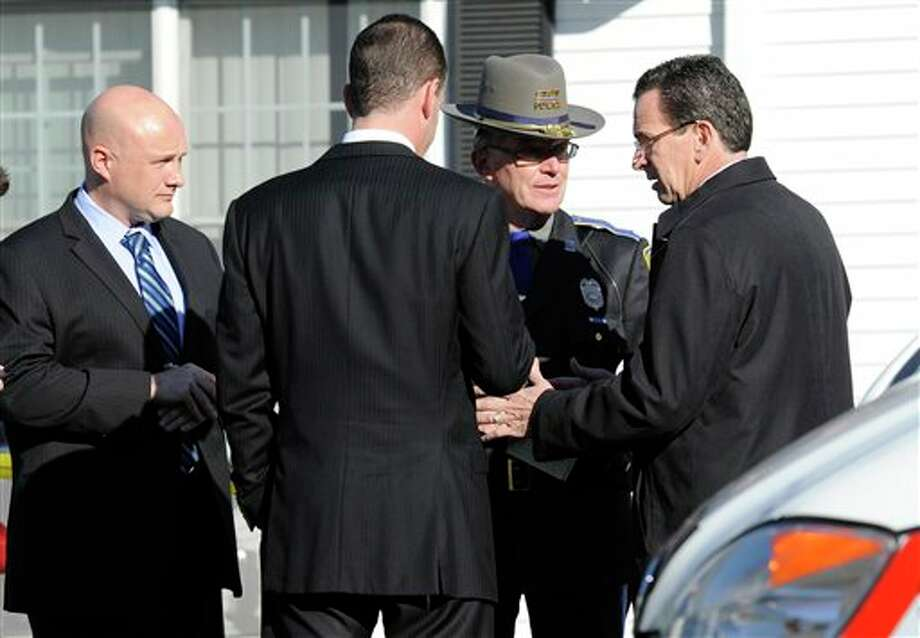 Gov. Dannel P. Malloy, right, talks with officials at a staging area following a shooting at the Sandy Hook Elementary School in Newtown, Conn., about 60 miles (96 kilometers) northeast of New York City, Friday, Dec. 14, 2012. An official with knowledge of Friday's shooting said 27 people were dead, including 18 children. (AP Photo/Jessica Hill) Photo: Jessica Hill, ASSOCIATED PRESS / A2012