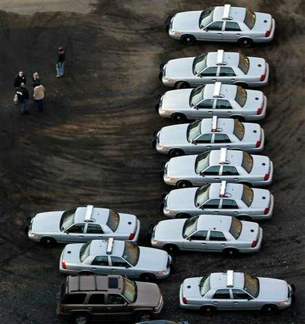 Police vehicles are lined up near a triage near Sandy Hook Elementary School in Newtown, Conn., where authorities say a gunman opened fire inside an elementary school in a shooting that left 27 people dead, including 18 children, Friday, Dec. 14, 2012. (AP Photo/Julio Cortez) Photo: Julio Cortez, ASSOCIATED PRESS / AP2012