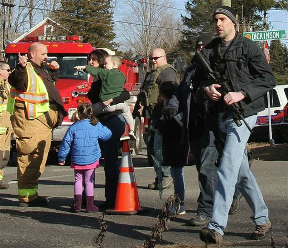 A law enforcement official carries a weapon as he walks past firefighters and parents with their children after a shooting at the Sandy Hook Elementary School in Newtown, Conn. on Friday, Dec. 14, 2012. (AP Photo/The Journal News, Frank Becerra Jr.) NYC OUT, NO SALES, TV OUT, NEWSDAY OUT; MAGS OUT; MANDATORY CREDIT: THE JOURNAL NEWS, FRANK BECERRA JR. Photo: Frank Becerra Jr., AP / The Journal News