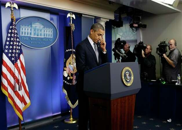 President Barack Obama wipes his eye as he speaks about the school shooting in Newtown, Conn., Friday, Dec. 14, 2012, in the briefing room of the White House in Washington. (AP Photo/Charles Dharapak) Photo: Charles Dharapak, AP / AP