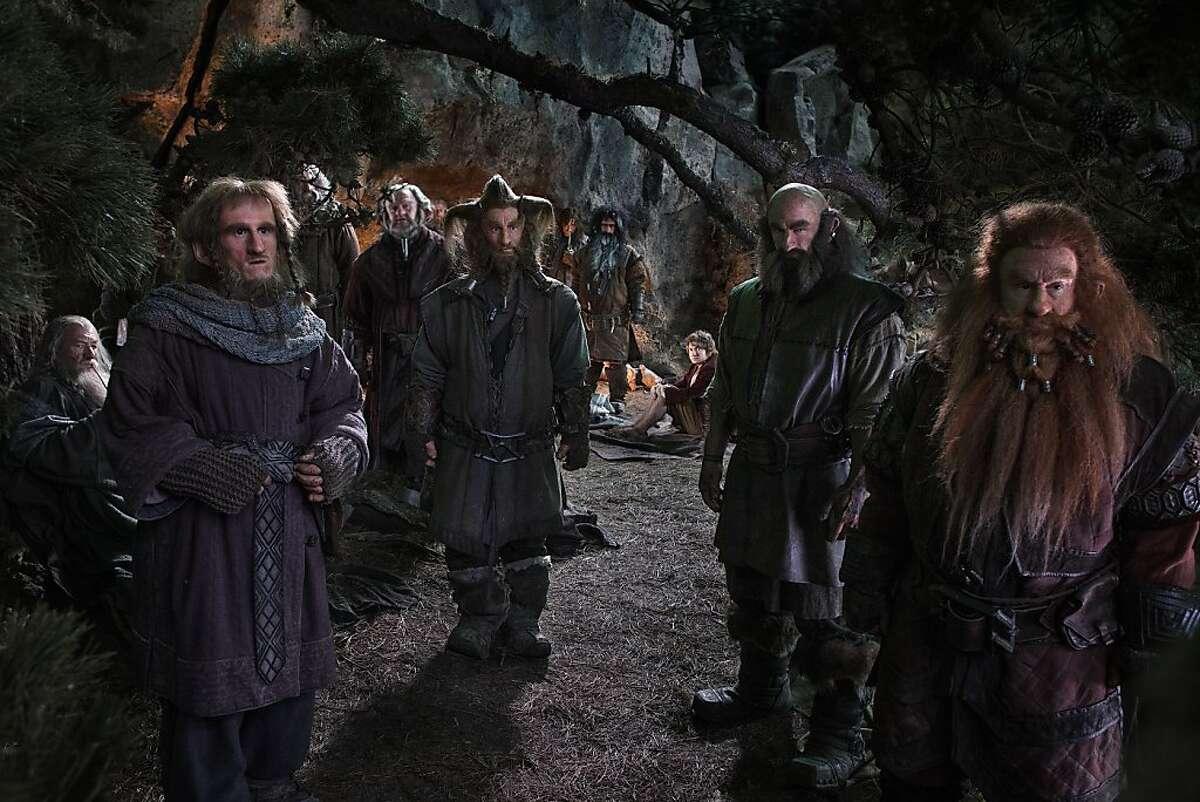 "Ian McKellen, left, as Gandalf with an assortment of dwarves in ""The Hobbit: An Unexpected Journey."""