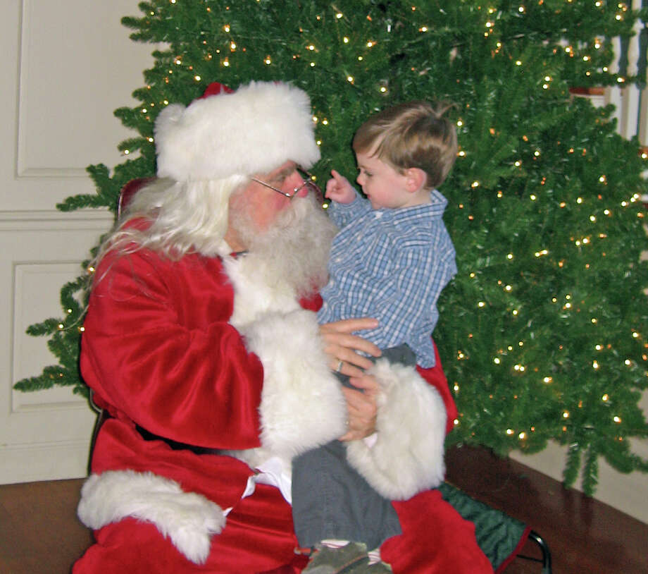 Santa listens closely as Cavin Kennedy goes through his wish list. Santa will visit Momís Morning In at the Darien Community Association on Dec. 21. Photo: Contributed