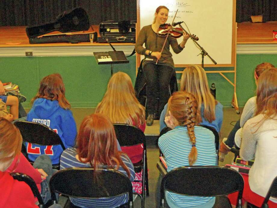 Accomplished folk musician Sara Milonovich plays for a group of Middlesex Middle School students as part of visiting artist program. Photo: Contributed