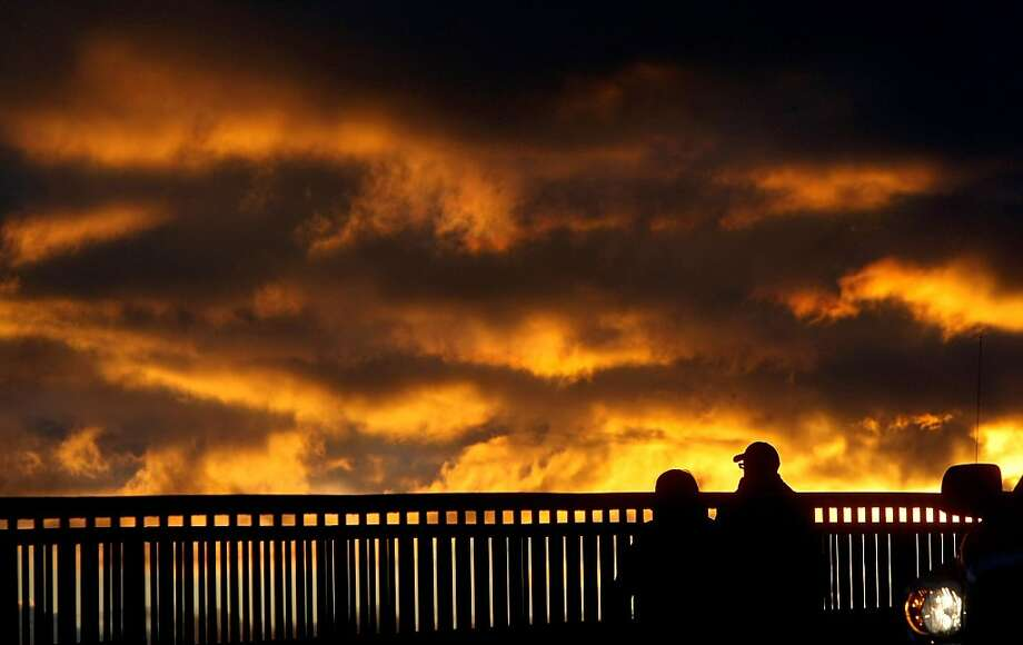 Storm clouds open up at sunset, creating a golden glow over the Manette Bridge in Bremerton, Wash. Photo: Larry Steagall, Associated Press