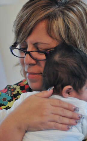 Arlene Saenz of Respite Care of San Antonio hugs an infant at the facility. Photo: Robin Jerstad/For The Express-Ne