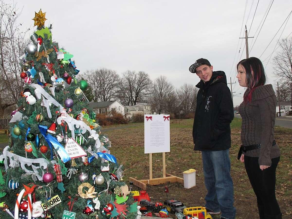 Dan Canales and Ashley Papa admire an artificial Christmas tree that was saved in Union Beach, N.J.