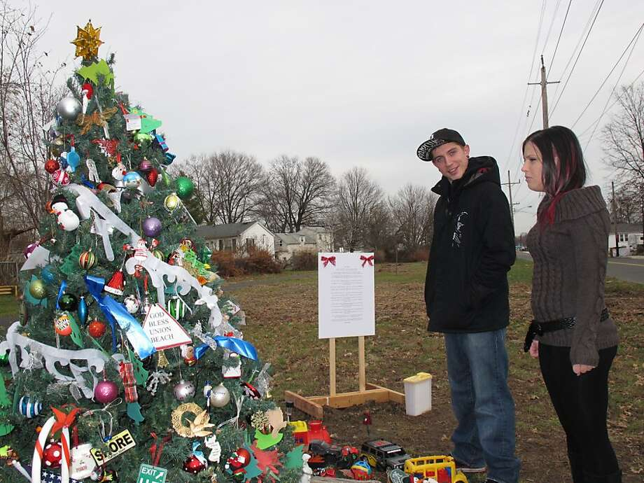 Dan Canales and Ashley Papa admire an artificial Christmas tree that was saved in Union Beach, N.J. Photo: Wayne Parry, Associated Press