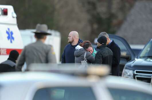 Police stand before grieving residents following a shooting December 14, 2012 at Sandy Hook Elementary School on December 14, 2012 in Newtown, Connecticut. At least 26 people, including 20 young children, were killed when a gunman assaulted the school and another body was found dead at a second linked crime scene, police said.  Police spokesman Lieutenant Paul Vance told reporters that the attacker killed 20 children and six adults, including someone that he lived with, at the Sandy Hook Elementary School in Newtown, Connecticut.  The gunman also died at the scene, and a 28th body was found elsewhere.