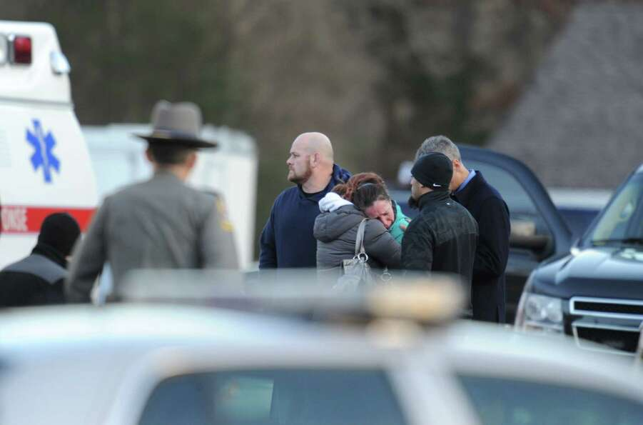 Police stand before grieving residents following a shooting December 14, 2012 at Sandy Hook Elementa